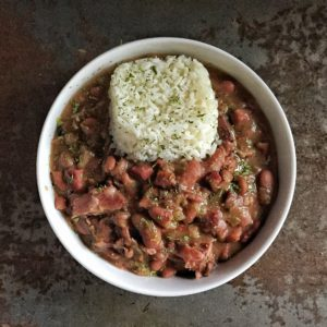 A bowl of red beans topped with white rice and parsley flakes