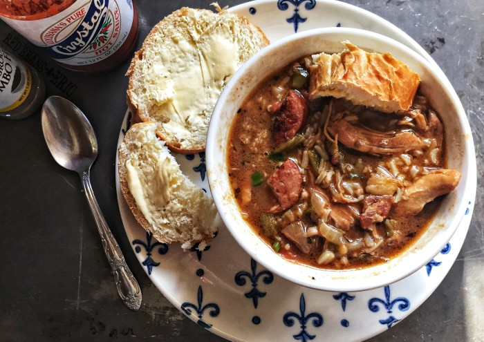 Bowl of chicken and sausage gumbo with a bottle of Crystals hot sauce